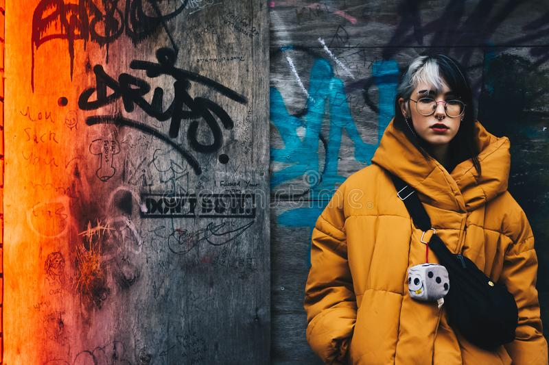 Woman in Yellow Coat With Black Crossbody Bag Closing Her Eyes stock images