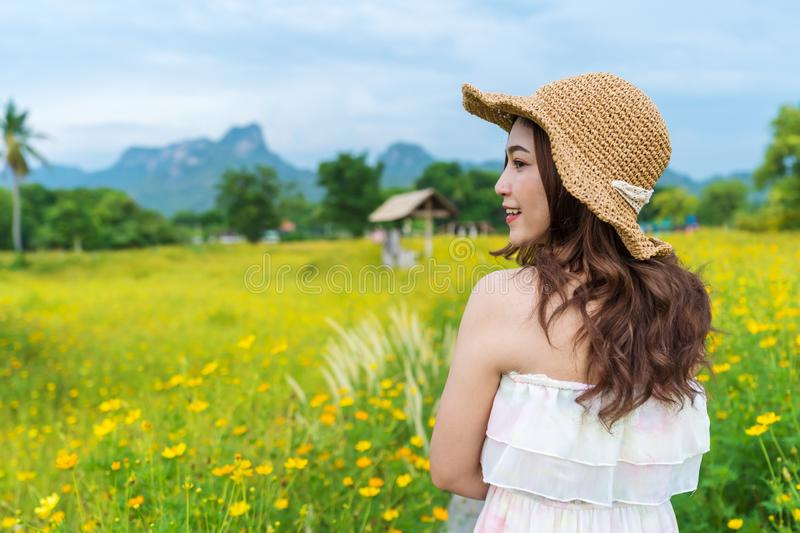 Woman in yellow cosmos flower field stock photography