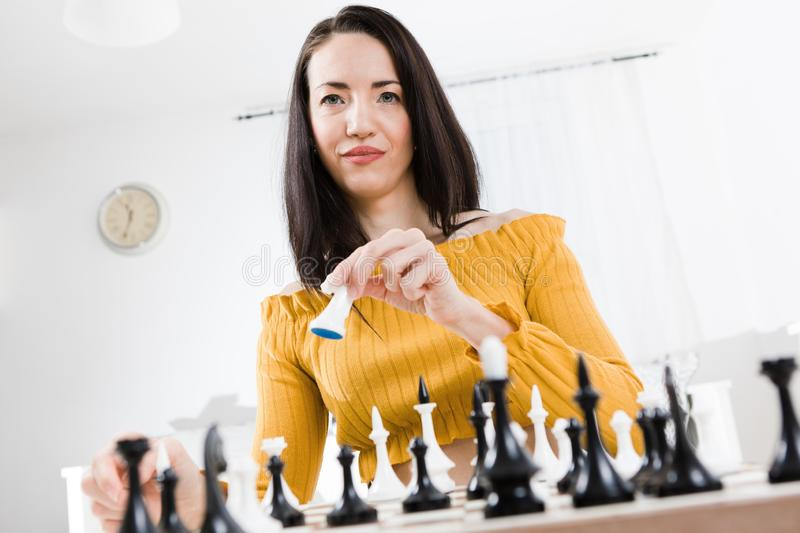 Woman in yellow dress sitting in front of chessboard. Going to move white horse stock images