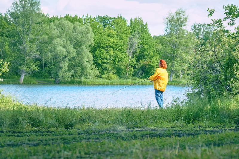 Woman in yellow jacket fishing spinning on lake stock image