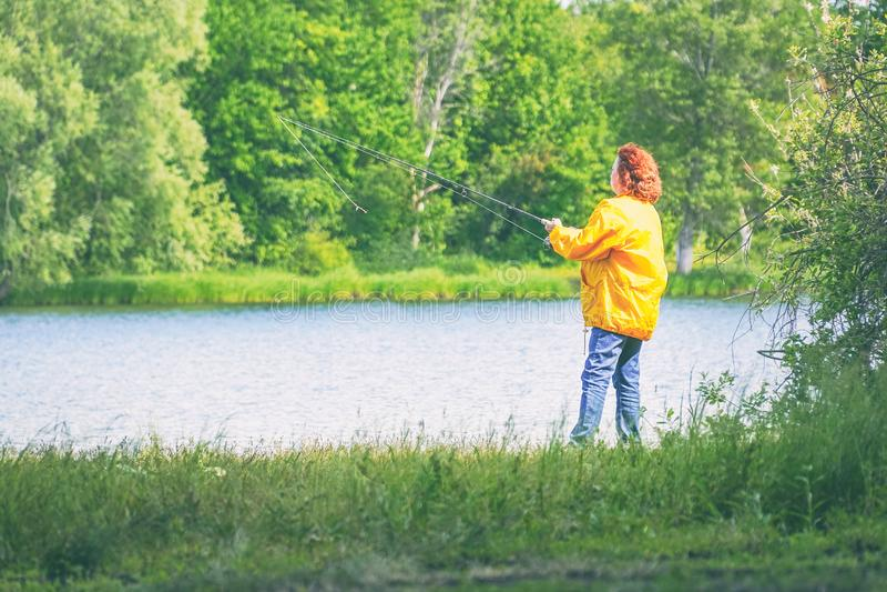 Woman in yellow jacket fishing spinning on lake royalty free stock photos