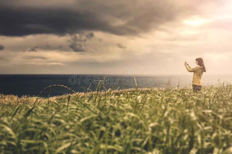 Beautiful winter day. Woman with a yellow jacket looking to the ocean stock images