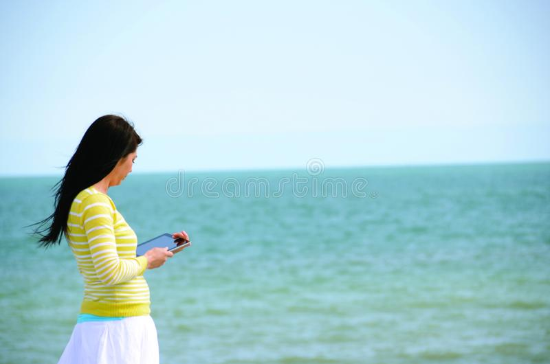 Woman In Yellow Long Sleeved Shirt And White Skirt Walking On Seashore royalty free stock image