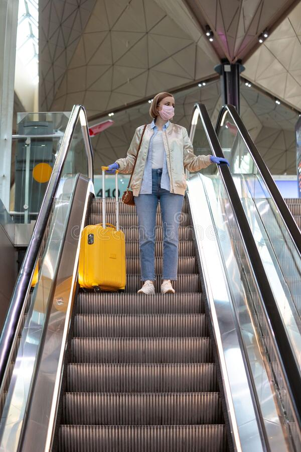 Woman with yellow luggage stands on escalator at almost empty airport terminal due to coronavirus pandemic. /Covid-19 outbreak travel restrictions. Flight stock photos