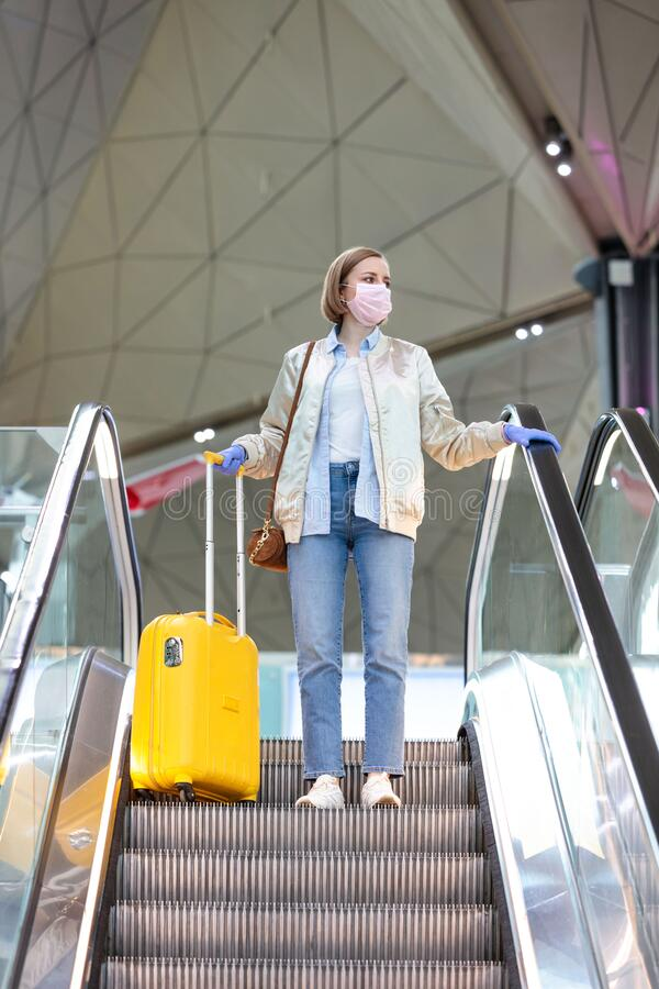 Woman with yellow luggage stands on escalator at almost empty airport terminal due to coronavirus pandemic/Covid-19. Outbreak travel restrictions. Flight stock photography