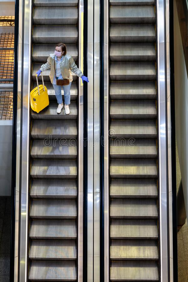 Woman with yellow luggage stands on escalator at almost empty airport terminal due to coronavirus pandemic, top view. Woman with yellow luggage stands on royalty free stock image