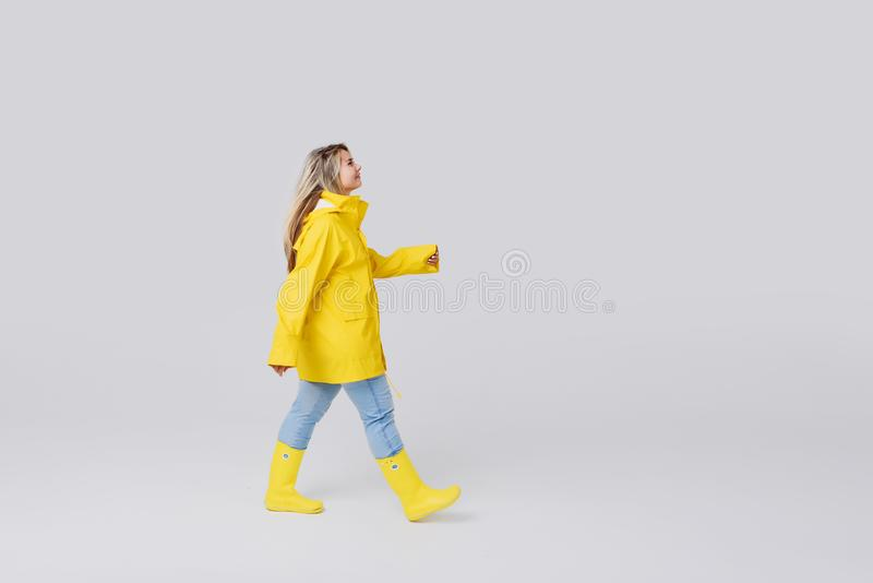 Woman in a yellow raincoat on a gray background. Young woman blonde in a yellow raincoat and yellow rubber knee-boots on a white background. Gladly steps after a royalty free stock images