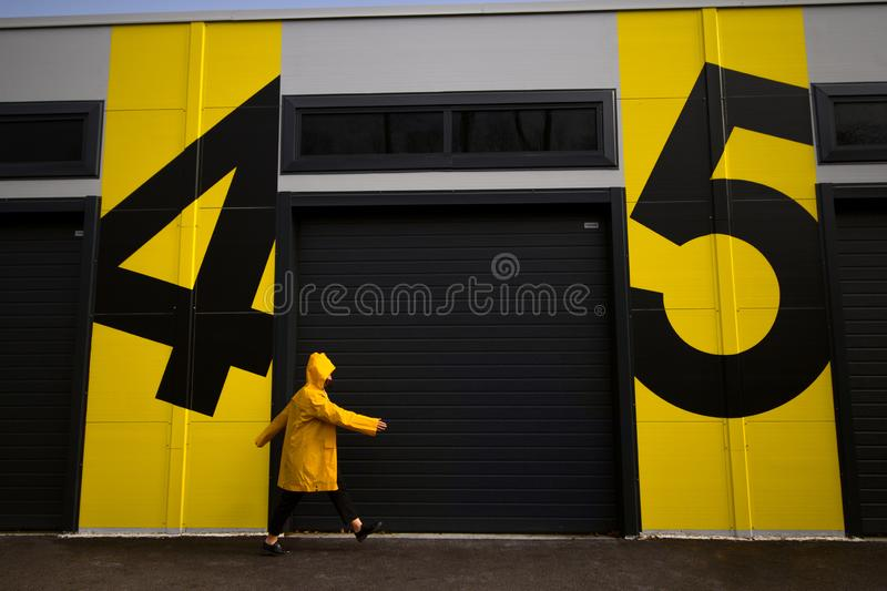 woman in raincoat walking from number four to number five stock photography