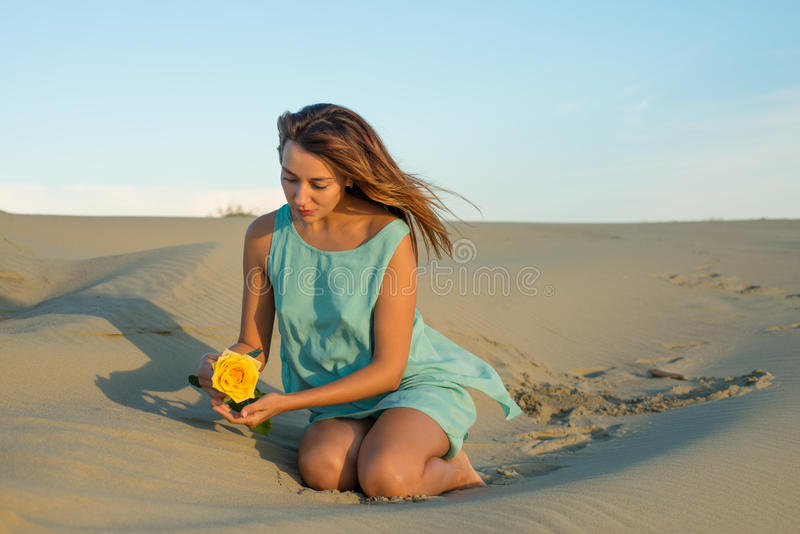 Download Woman With A Yellow Rose Sits On The Sand Stock Photo - Image: 34225152
