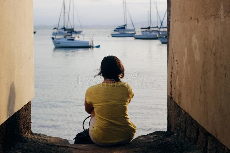 Woman in Yellow Shirt Sitting Near Body of Water royalty free stock images