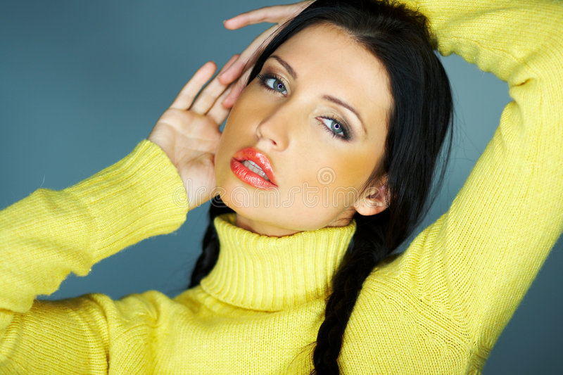 Woman with yellow sweater. Portrait of black haired woman with yellow jumper or sweater, studio background royalty free stock image