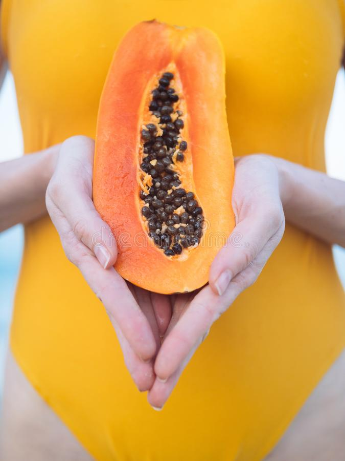 Woman in yellow swimsuit with exotic fruit papaya on the beach at sunrise royalty free stock photography