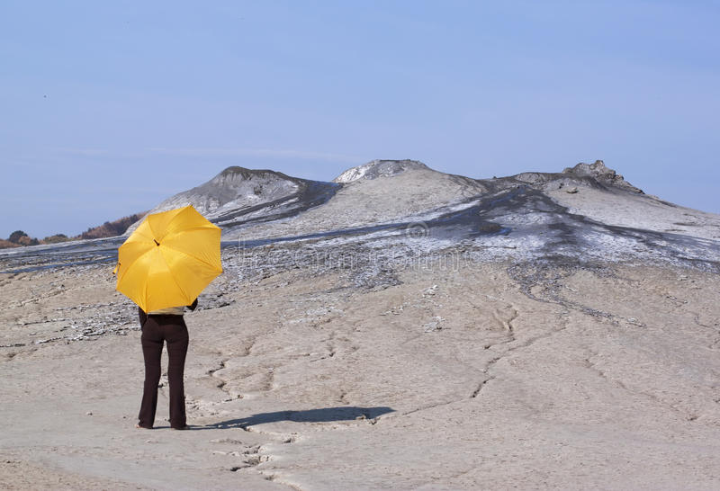 Woman with yellow umbrella. Woman with a yellow umbrella in a dry ground looking to a muddy volcano stock image