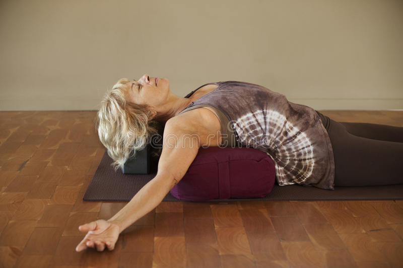 Woman On Yoga Bolster. Middle aged woman resting on a yoga bolster in a restorative posture stock images