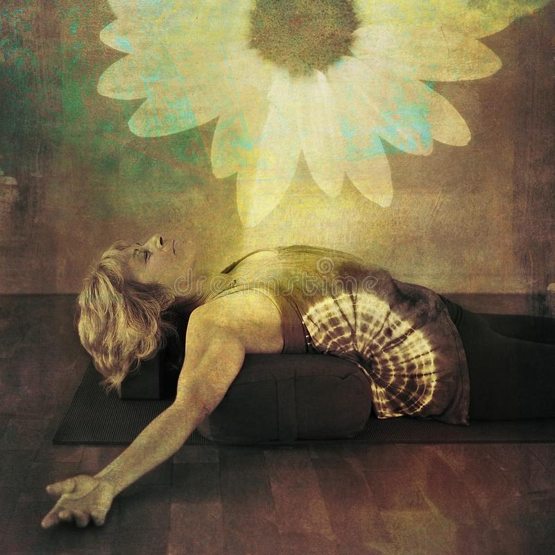 Woman On Yoga Bolster. Middle age woman resting on a yoga bolster experiencing a bloom of light in her being stock photography
