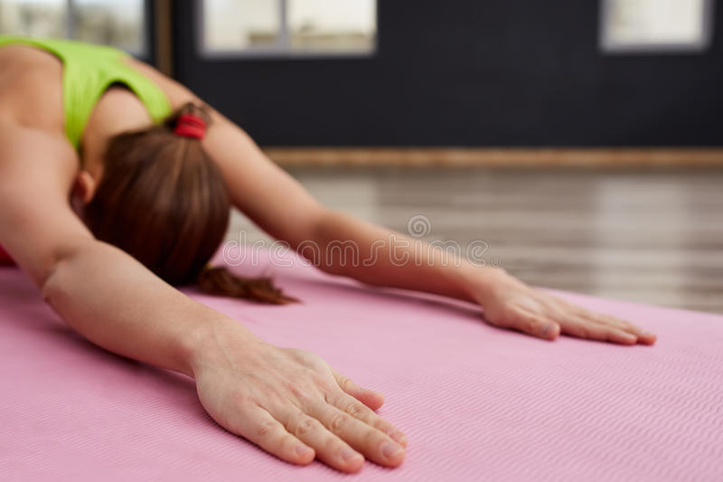 Woman on yoga class indoor closeup of hands in relaxing pose. Sporty woman with long hear in sporty clothes. On the pink yoga mat. Closeup of the hands stock photography