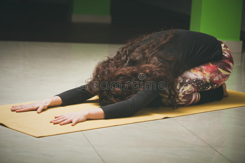 Woman on yoga class in rest pose indoor. Healthy lifestyle concept royalty free stock photography