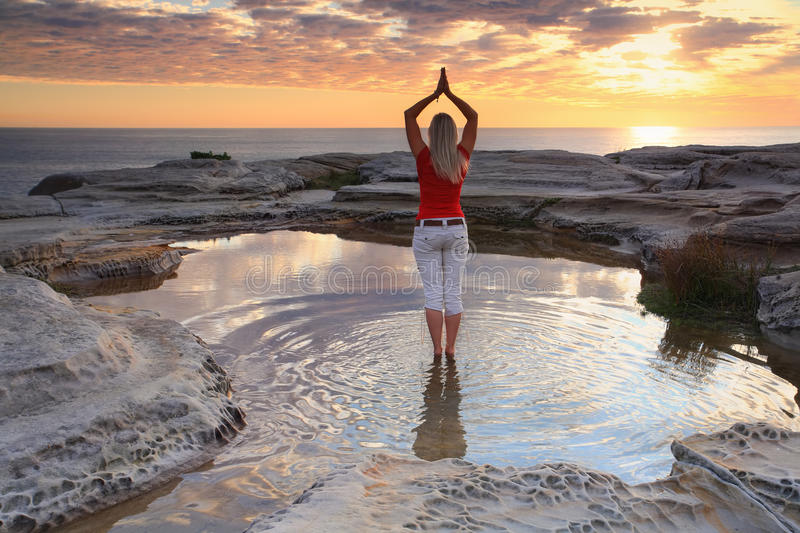Woman yoga meditation by the ocean sunrise stock photography