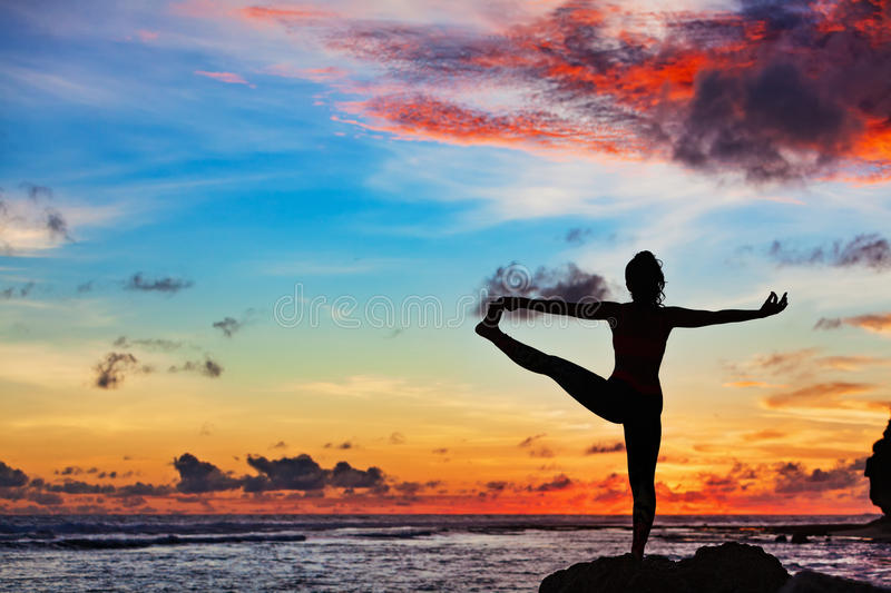 Woman in yoga pose on sea beach rock. Sunset meditation silhouette. Active woman stand in yoga pose on beach rock to keep fit and health. Healthy lifestyle stock images