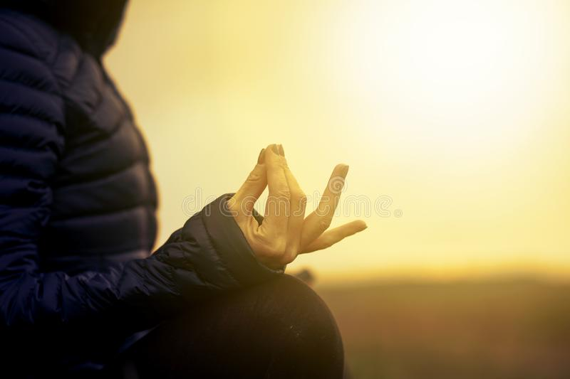Woman in a yoga pose at sunset - mindfulness, meditation, mental health royalty free stock image