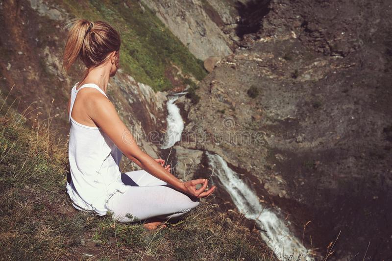 Woman in yoga positiion looks at waterfall stock images