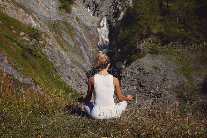 Woman in yoga position. Peace among the mountain stock photos