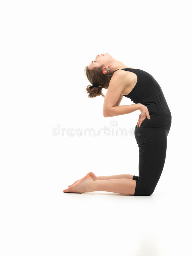 Woman in yoga posture. Young attractive woman in balancing yoga pose, side view, dressed in black on white background stock image