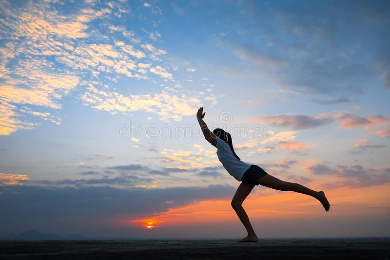 Young woman yoga at sunset. The woman with yoga posture on the mountain at sunset; Silhouette of gorgeous young woman practicing yoga outdoor royalty free stock images