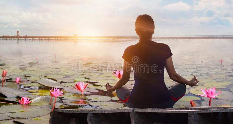 Woman yoga practicing and meditating by the red lotus lake background royalty free stock photos