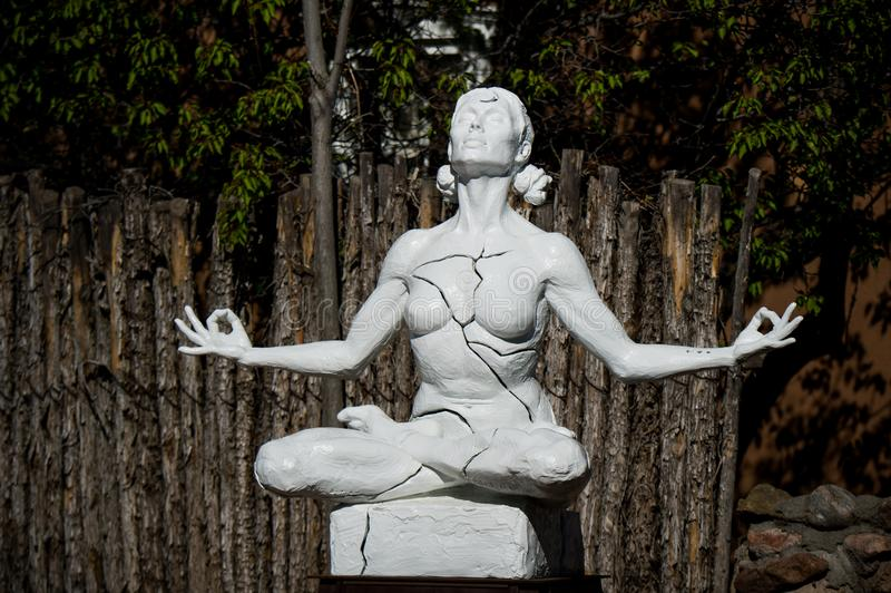 No stress. Woman Yoga - relax in nature. Statue of a woman who is meditating as seen in Canyon Road Street in Santa Fe stock photography