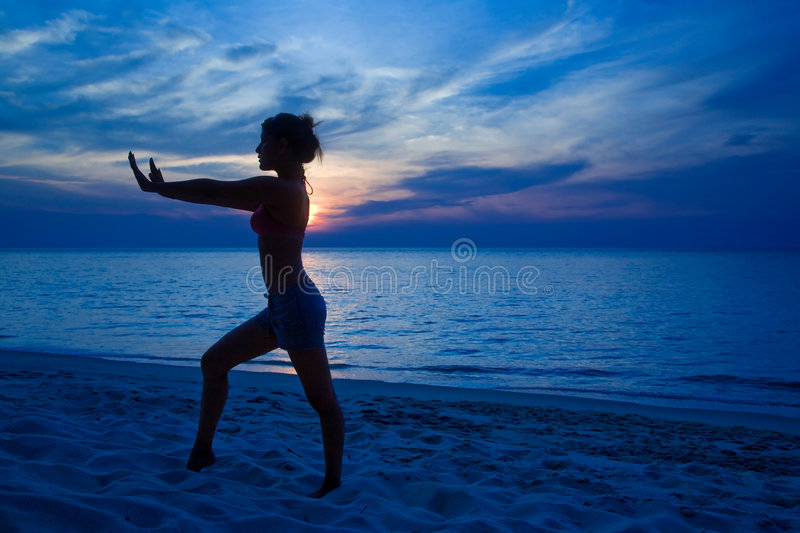 Woman Yogaing By The Sunset Beach Royalty Free Stock Image