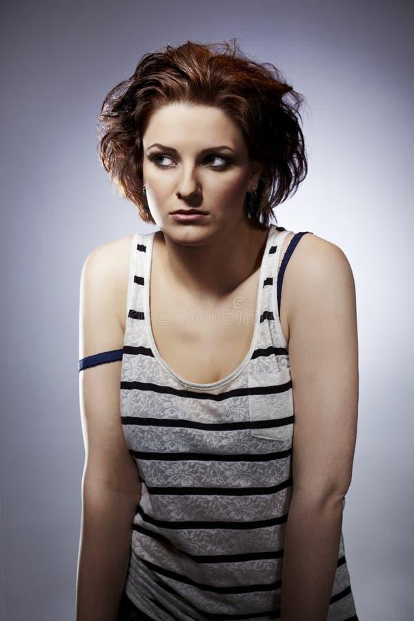 Woman - young brunette beauty in studio. Young woman on indoor location posing as drug addict. Female smoking marijuana in studio stock photo