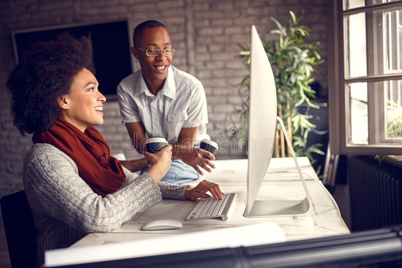 Woman with young co-worker in project office at work royalty free stock photography