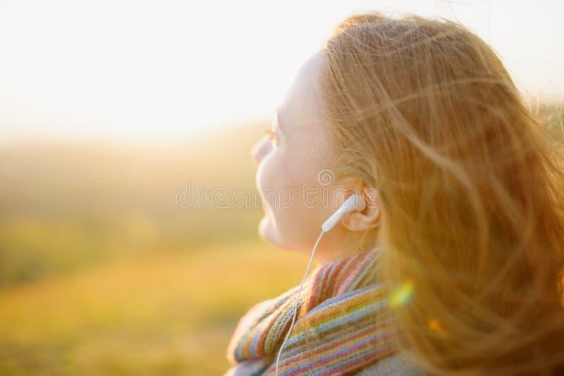 Young woman enjoying a music in the fall season stock photos