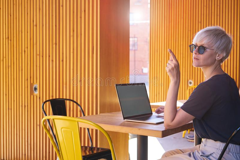 Woman young entrepreneur with short hair working on laptop, screen space for design layout. Sitting outside in cafe, yellow royalty free stock photography