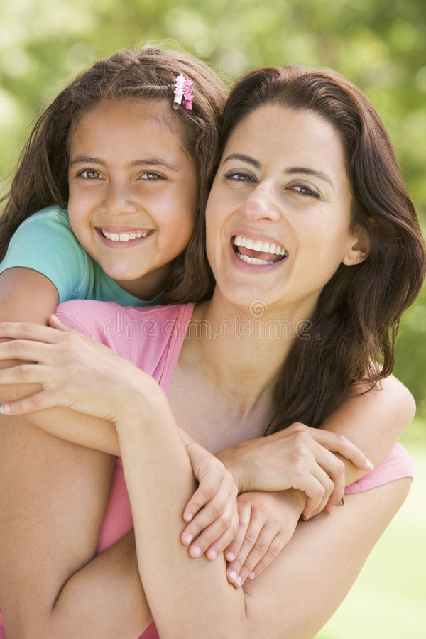 Woman and young girl embracing outdoors smiling royalty free stock images