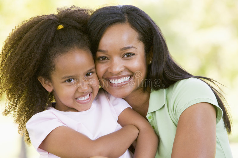 Woman and young girl outdoors embracing royalty free stock images