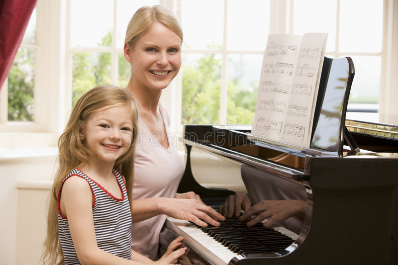 Woman and young girl playing piano and smiling royalty free stock image