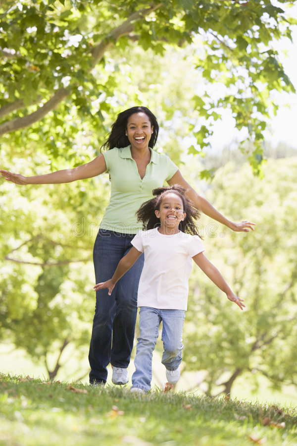 Woman and young girl running outdoors smiling stock photography