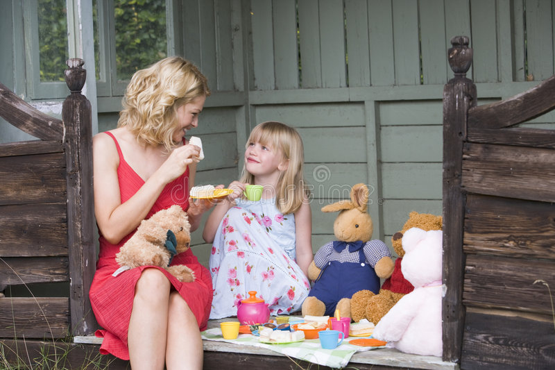 Woman and young girl in shed playing tea stock images