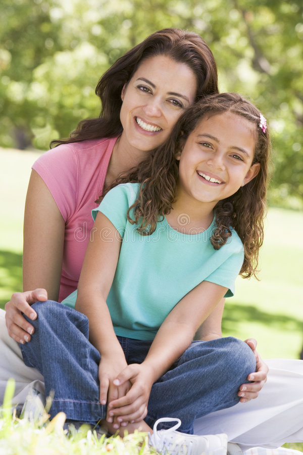 Woman and young girl sitting outdoors smiling stock photography