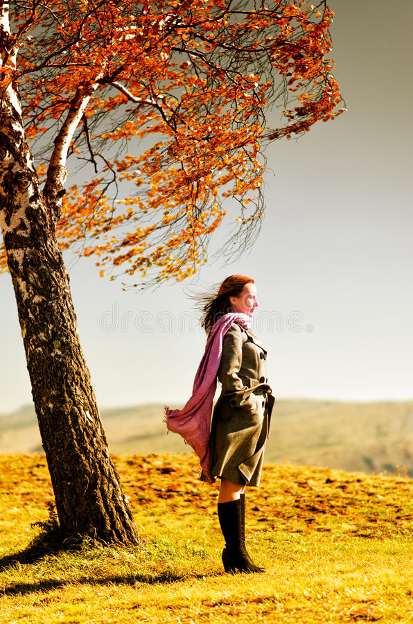 Young woman standing on an autumn hill royalty free stock photo