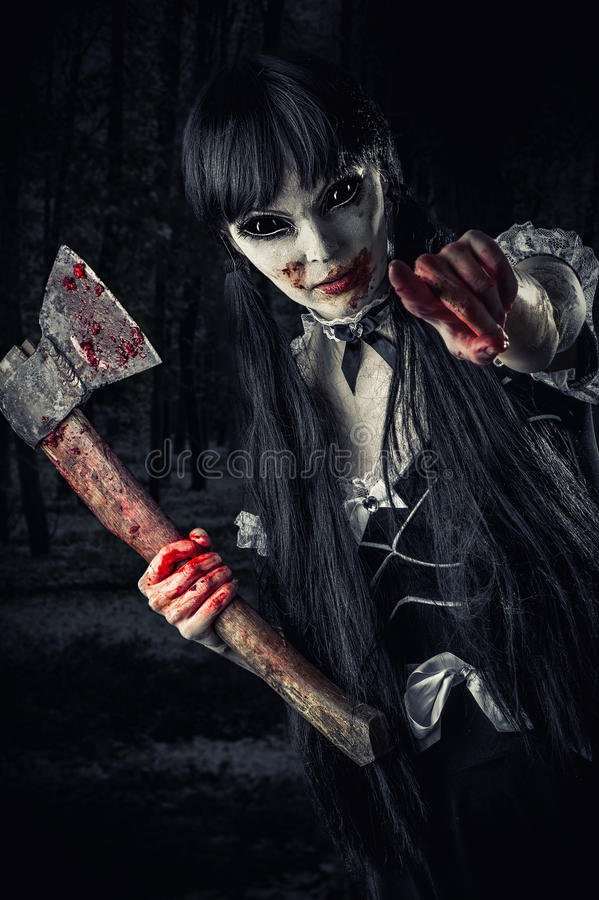 Woman zombie with bloody axe. Extends hand to shot and pointing at you. Halloween concept. Evil ghost in night forest royalty free stock photos