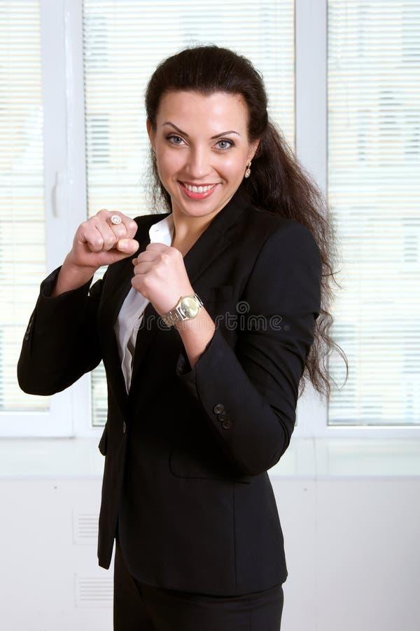 Womanin svärtar ställningar för affärsdräkt som en boxare arkivbilder