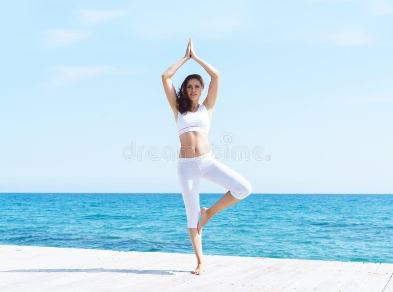 Womanm in der weißen sportlichen Kleidung, die auf einem hölzernen Pier auf SU-Meer und Himmelhintergrund meditiert lizenzfreies stockfoto