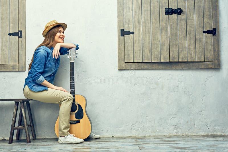 Womann sammanträde på bänk med gitarren arkivfoto