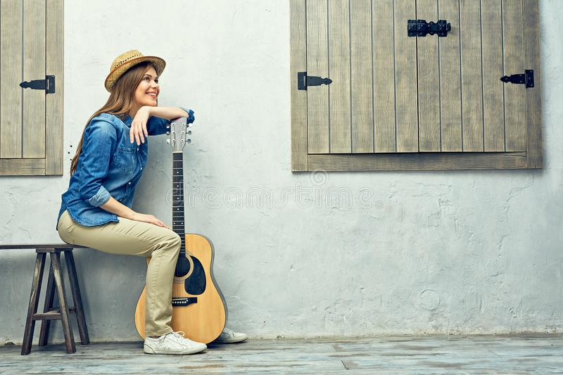 Womann sitting on bench with guitar. stock photo