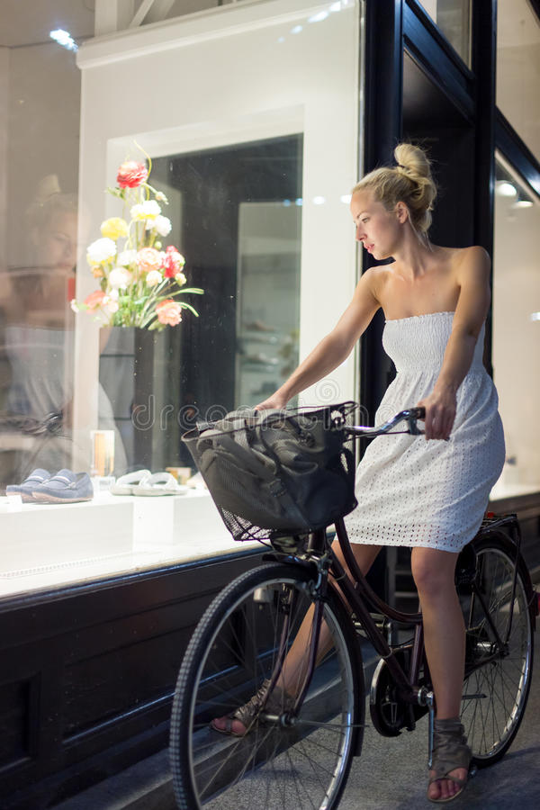 Womanon bicycle window shopping at night. stock photos