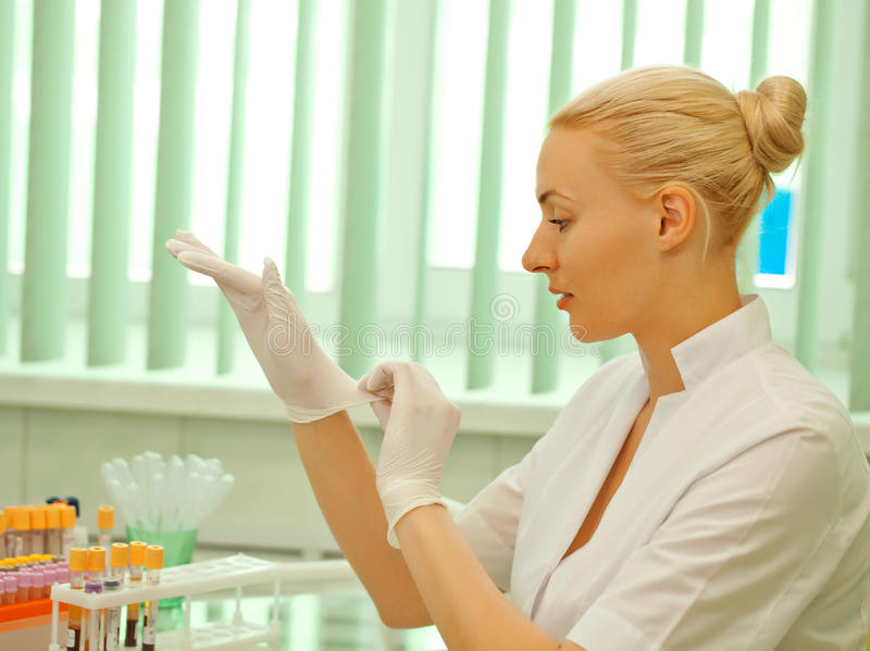 Womanputs för medicinsk doktor på latexhandskar arkivbild