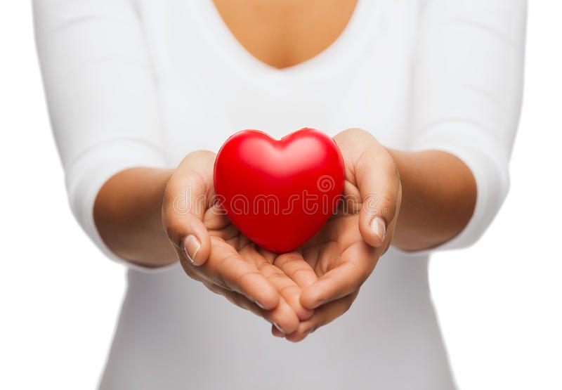 Womans cupped hands showing red heart. People, relationship and love concept - close up of womans cupped hands showing red heart royalty free stock photo